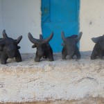 4 clay Bulls waiting to be pit-fired.