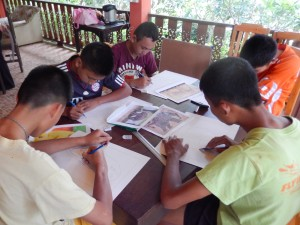 A group of young artists working on their sketches of elephants.