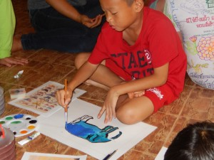 A young artist working on his blue elephant painting
