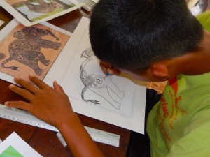 A young artist working on his sketch of a tattooed elephant