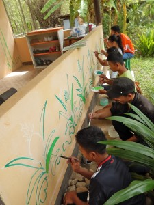 Young artists begin filling in the chalk sketch of pineapples for the mural.  This wall faces an open field that has many pineapple plants.
