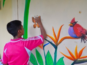 A young artist adds a butterfly to the mural